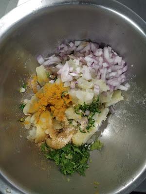 Adding chopped onion green chilli, turmeric powder,cumin powder with mashed potato for aloo paratha stuffing