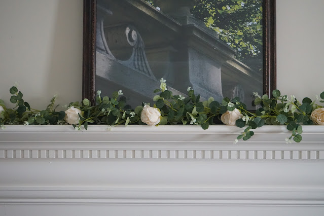 White mantel decorated with blush rose garland