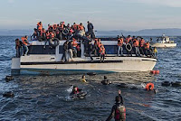 Syrian and Iraqi refugees arrive from Turkey to Skala Sykamias, Lesbos island, Greece. Volunteers (life rescue team - with yellow-red clothes) from the Spanish NGO Proactiva Open Arms help the refugees. Foto: Ggia, via Wikimedia. Lisens: CC by-sa 4.0