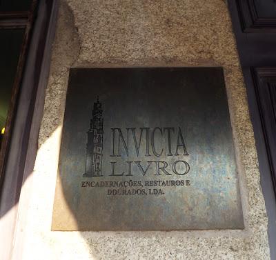 Placa de ferro em parede escrita Invicta Livro