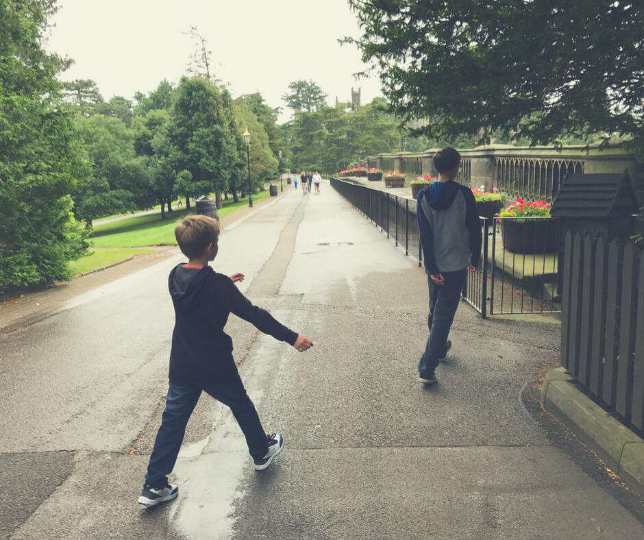 Two boys walk away from the camera towards a castle at Alton Towers theme park.