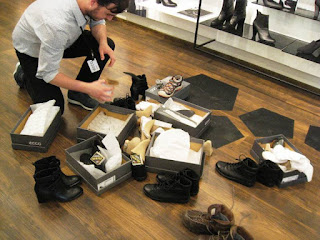 Shop assistant surrounded by many shoes