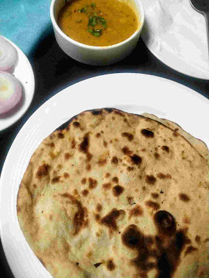 Serving tandoori roti in a plate, onion slices and dal in background