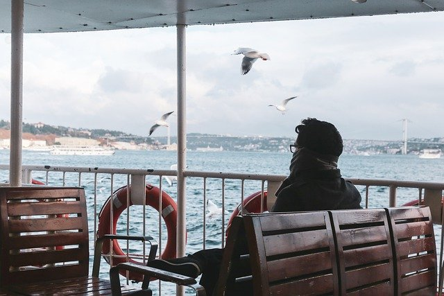 Seorang pria duduk sendirian diatas kapal