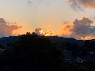 A photograph of a golden sunset over a dark hill.