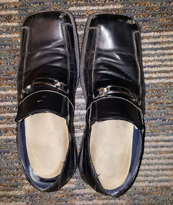 A pair of men's black dress shoes on the floor, seen from above.