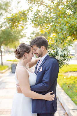 bride and groom hugging with flowers