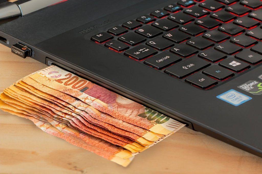 Notas de dinheiro ao lado do notebook