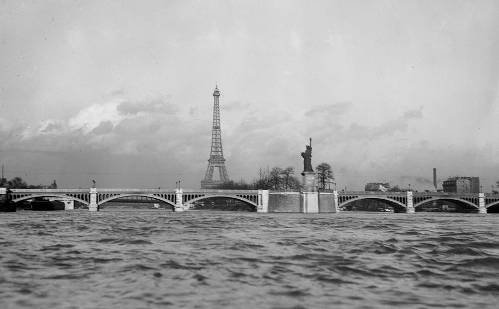 The Eiffel Tower and a replica of the Statue of Liberty on Île aux Cygnes in Paris in March of 1919.