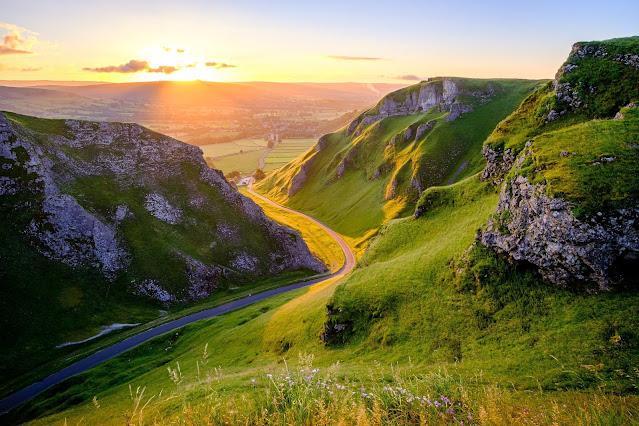 The sun sets over the steep, partially exposed limestone formations creating Winnats Pass