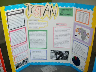 One of three group posters about Tostan