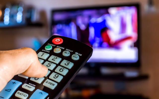 Homem vendo TV com controle remoto apontado para a tela