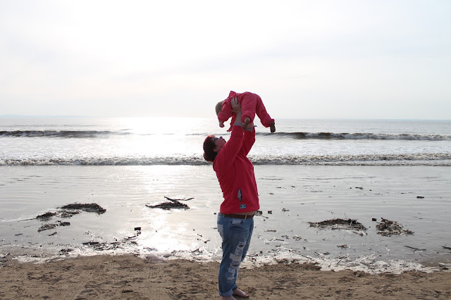 mother and baby photo shoot at beach holding baby up in the air