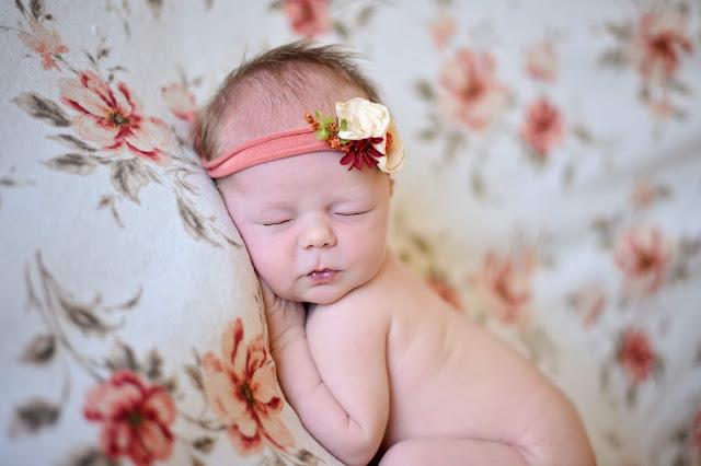Close up of newborn girl on flower blanket
