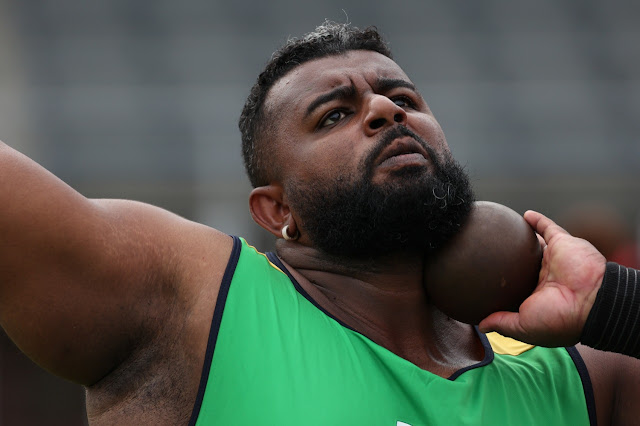 atleta negro e com barba de camisa verde com peso no queixo se prepara para arremessar peso