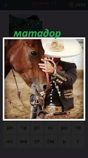 рядом с лошадью стоит матадор в белой шляпе и куртке с заклепками
