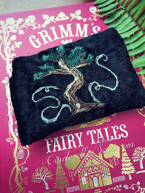 Thread Painted Magical Tree Wallet - This hand embroidered magical tree is based on a Grimm's fairy tale and decorates a soft velvet card holder wallet (or tea wallet) with a mother of pearl button closure. The perfect handmade gift for Lord of the Rings and fairy tale fans! Click to learn more about the wallet and artist #ent #lordoftherings #lothlorien #junipertree #enchantedforest #onceuponatime #embroideryart #threadpainting #textileart