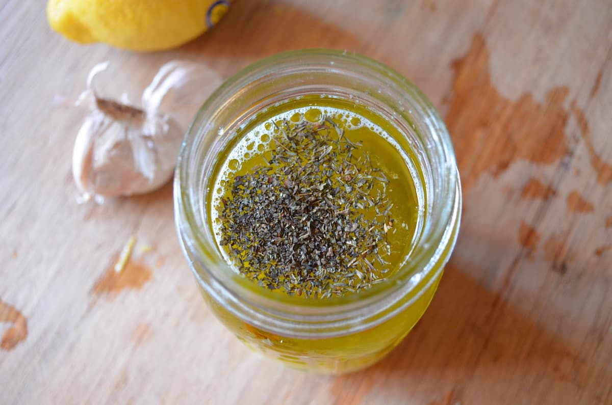 Lemon Vinaigrette Recipe in a jar on a wooden cutting board with garlic gloves and lemon in the background.
