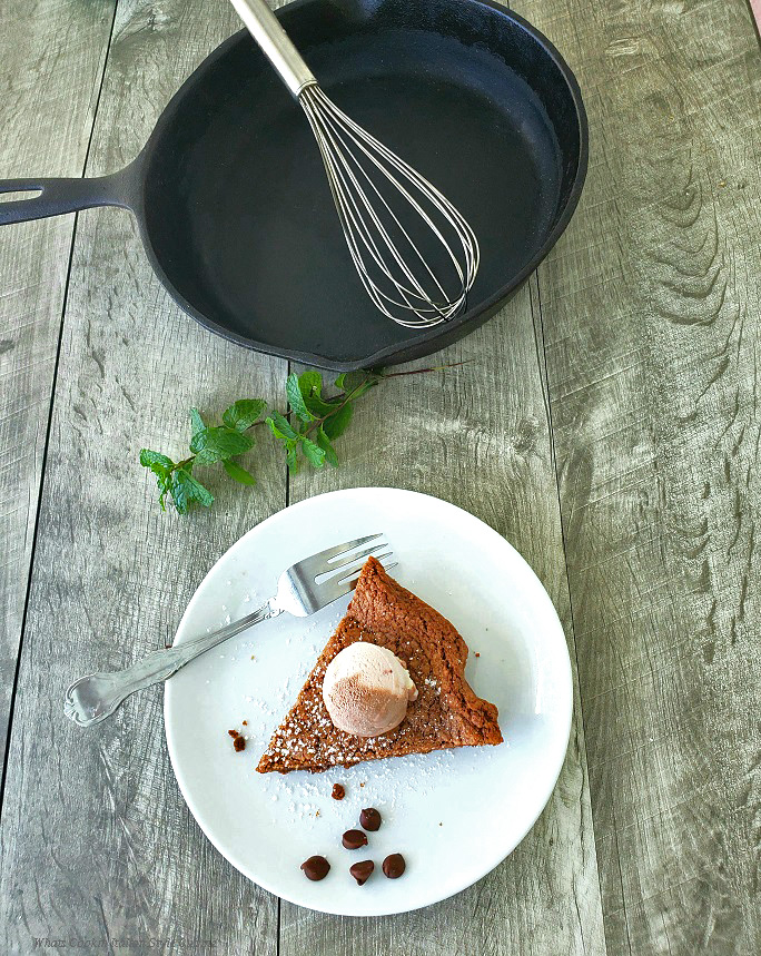 This is a sliced of chocolate skillet with a scoop of 3 flavored ice cream. This dessert is on a white place sprinkled with powdered sugar and has chocolate chips on the plate. In the background there is a fresh mint sprig and empty 10 inch cast iron skillet with a wire whisk is in the background along with sitting on a distressed piece of wood