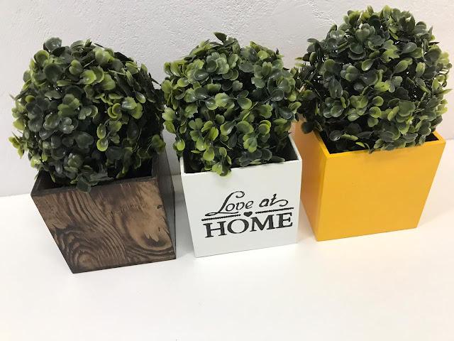 Três cachepots: marrom com pintura que imita madeira, amarelo e branco escrito love at home, com plantinhas artificiais do tipo buxinho.