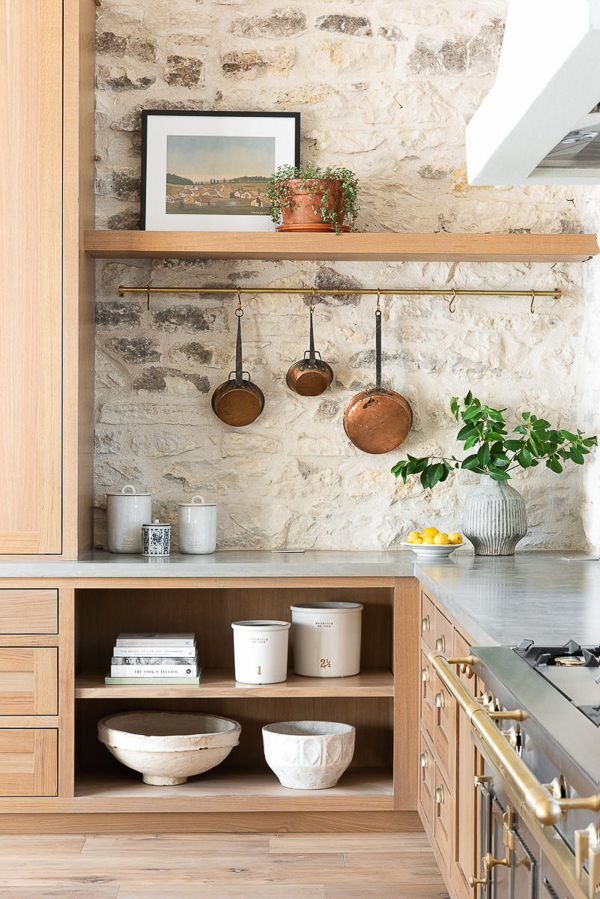 kitchen with light wood cabinets and stone wall with copper pots