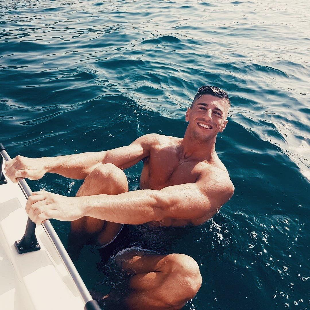 happy-hot-young-college-stud-smiling-getting-wet-ocean-swimming