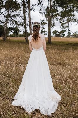 Novia vestida de blanco en un paisaje campestre