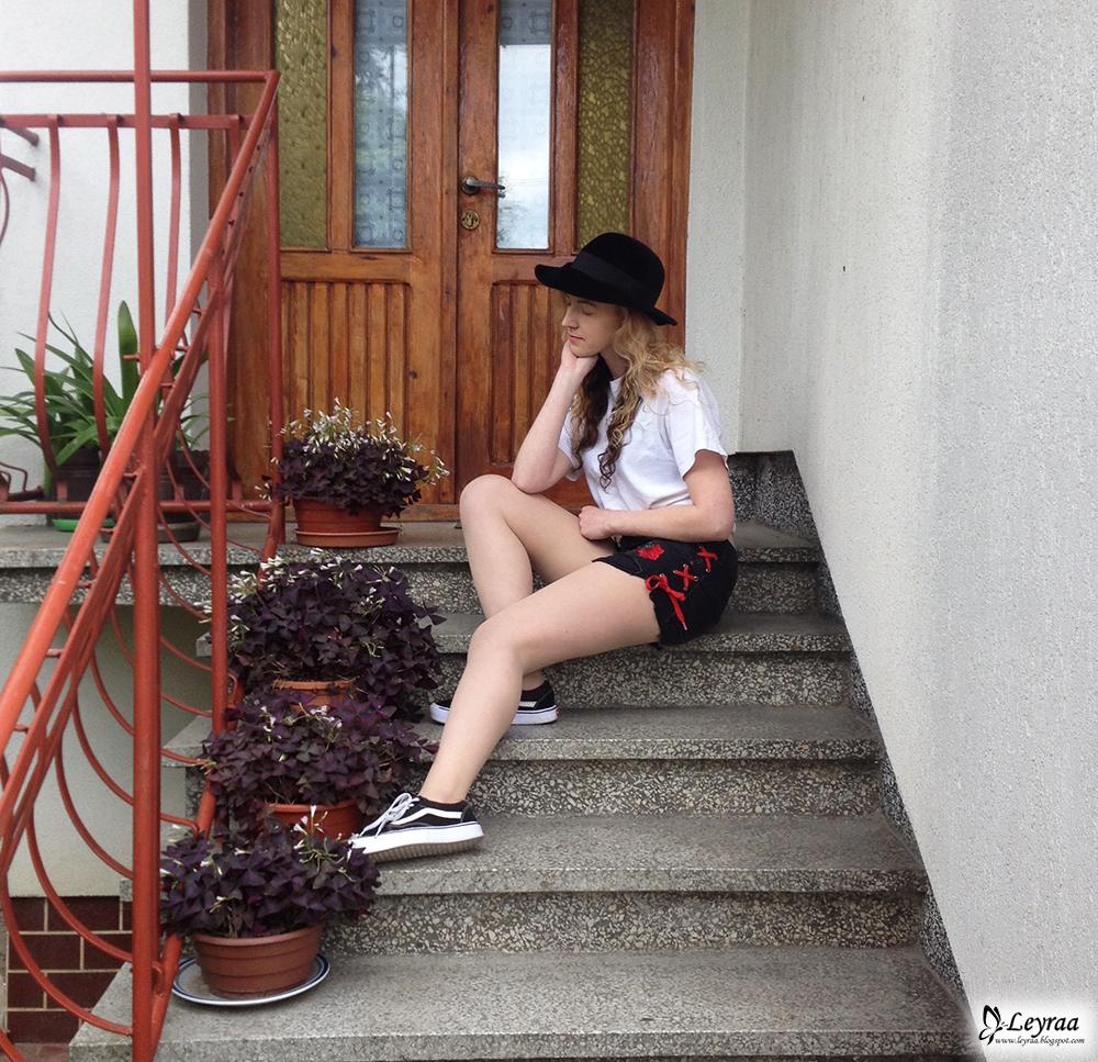 DIY szorty czarne z naszywkami różami i czerwonymi sznurkami, biała koszulka wiązana, kapelusz, trampki vans