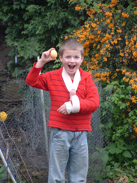 Photo of a little boy in a garden, holding up a dyed Easter egg with a huge smile