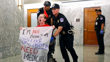 Photo of a disabled protester being forcibly removed by a law enforcement officer.