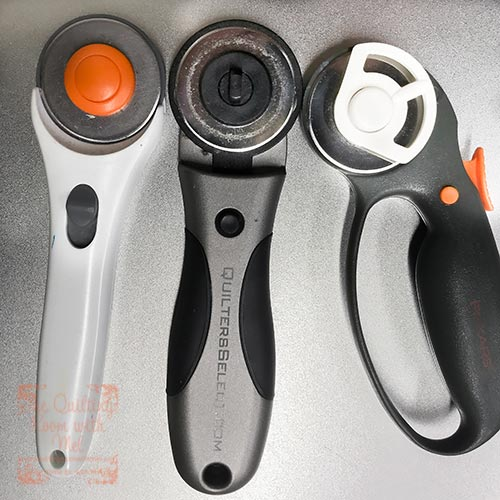 You need a rotary cutter to quickly and easily cut fabric.  These are three different 45 mm rotary cutters.
