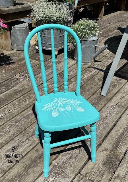 Photo of a wooden child's chair painted turquoise & stenciled with daisies
