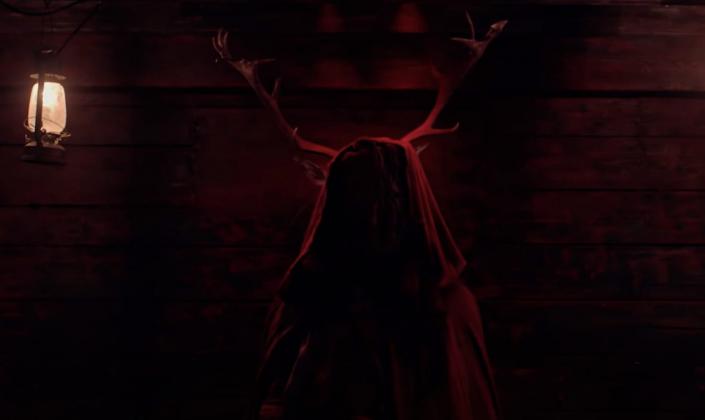 Imagem de capa: uma cabana de madeira iluminada por uma cor luz sangue, com uma placa de chifres de cervo na parede se projetando por trás de uma figura encapuzada de vermelho em pé e ao lado um lampião aceso com uma vela amarela brilhando fracamente.