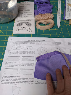 Hand holding piece of bra in progress next to pattern instructions