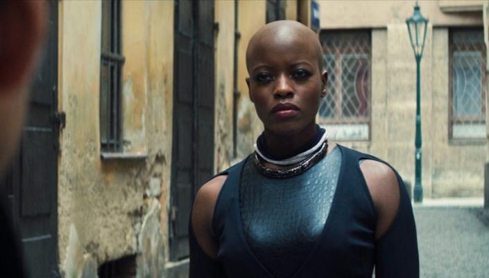Imagem: a personagem Ayo, uma mulher negra e com a cabeça raspada, os lábios com batom vermelho, em um traje preto, couro preto e um colar marrom, em uma rua de pedra com casas simples em tons amarelos.