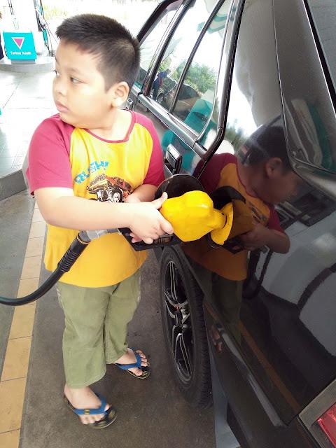 Along Izz membantu isikan minyak kereta.