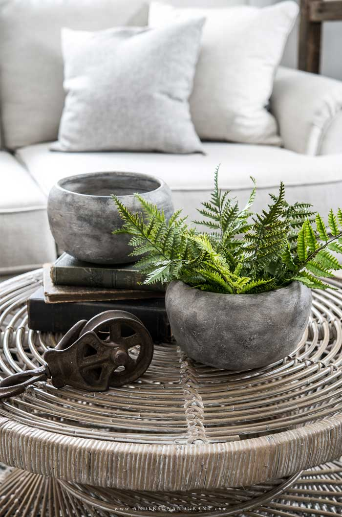 Pair of stone planters on wicker coffee table