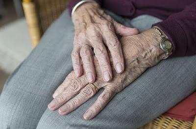 Närbild på äldre kvinnas händer som vilar i knät.