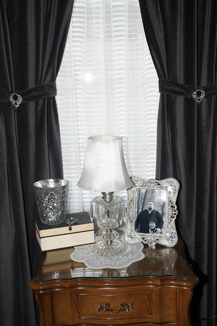 Charcoal gray curtains with diamond tie backs and night stand with stacked books