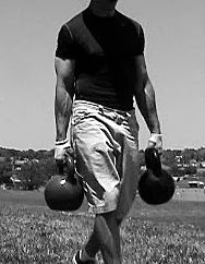 Image of a man performing the Farmer's Walk with kettlebells.