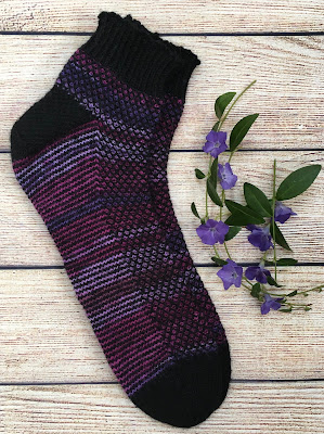 Hand-knitted socks placed next to purple flowers