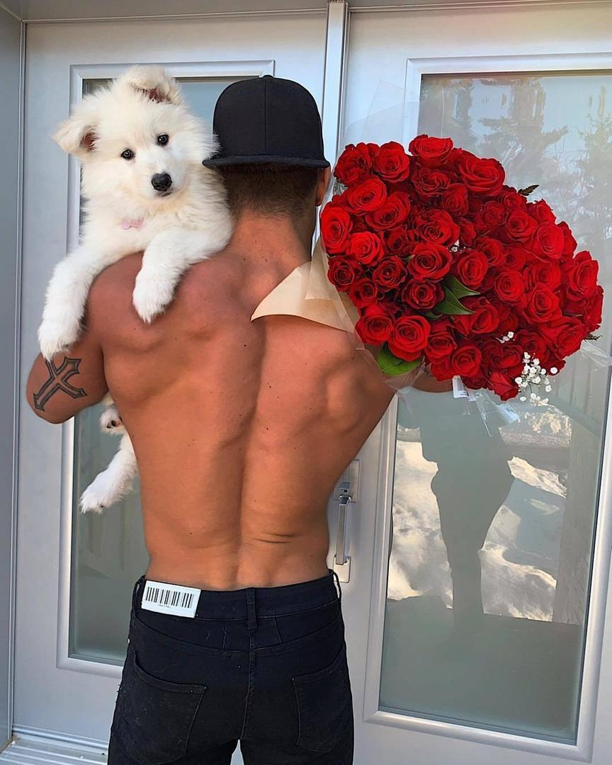 young-fit-shirtless-guy-huge-strong-back-red-flowers-white-dog