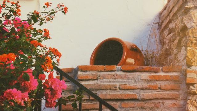 Pieza de alfarería tradicional y flores rosas y rojas