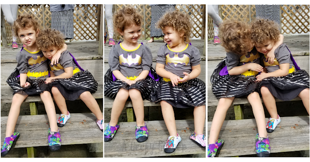 Three side by side photos of two blonde/brown haired curly haired toddler girls in matching Batgirl dresses