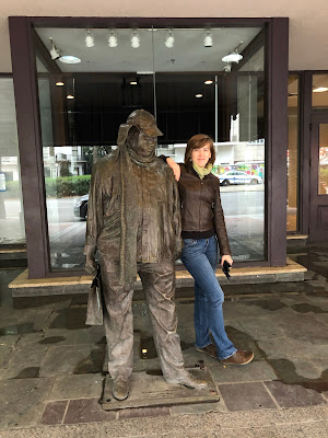 woman next to statue of a man