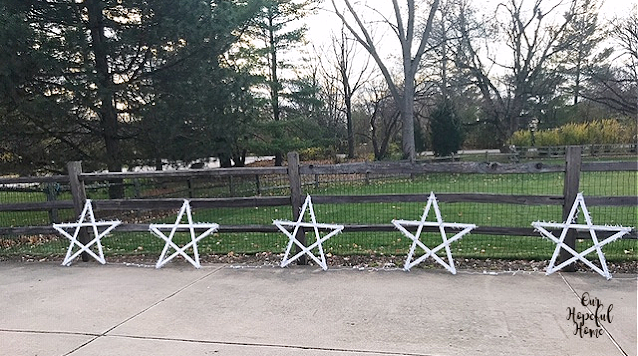 five DIY white painted wooden outdoor hanging stars