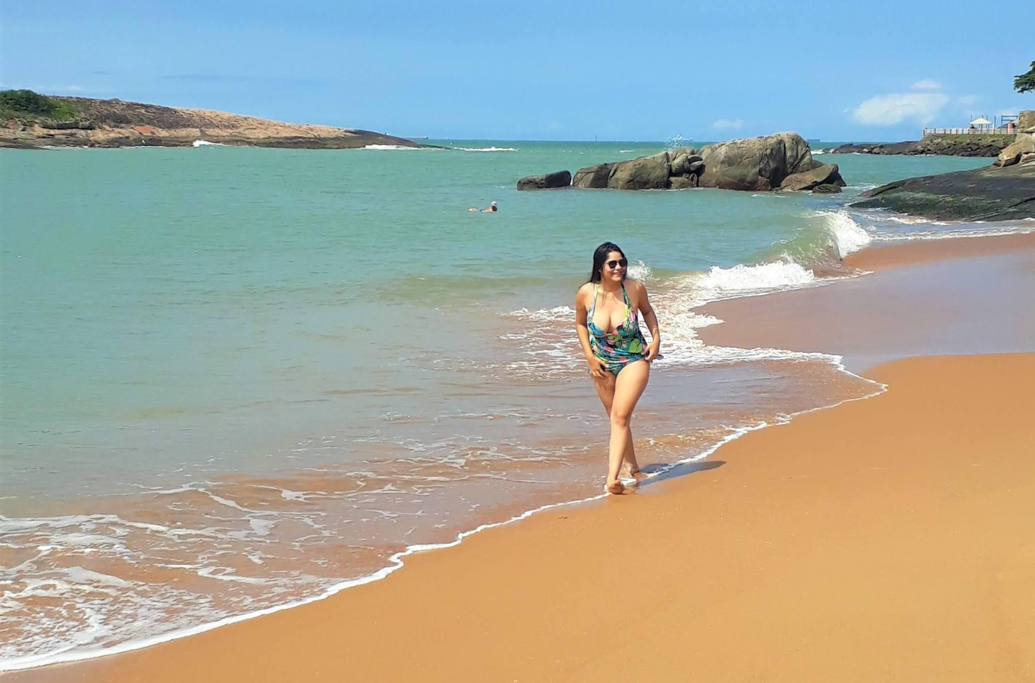 cartaz de uma moça andando na areia da praia