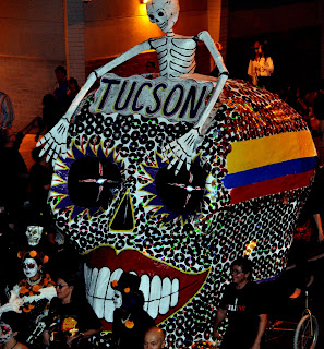 A giant bedazzled skull with a skeleton on top being pulled by costumed people. All Soul's Procession, Tucson AZ