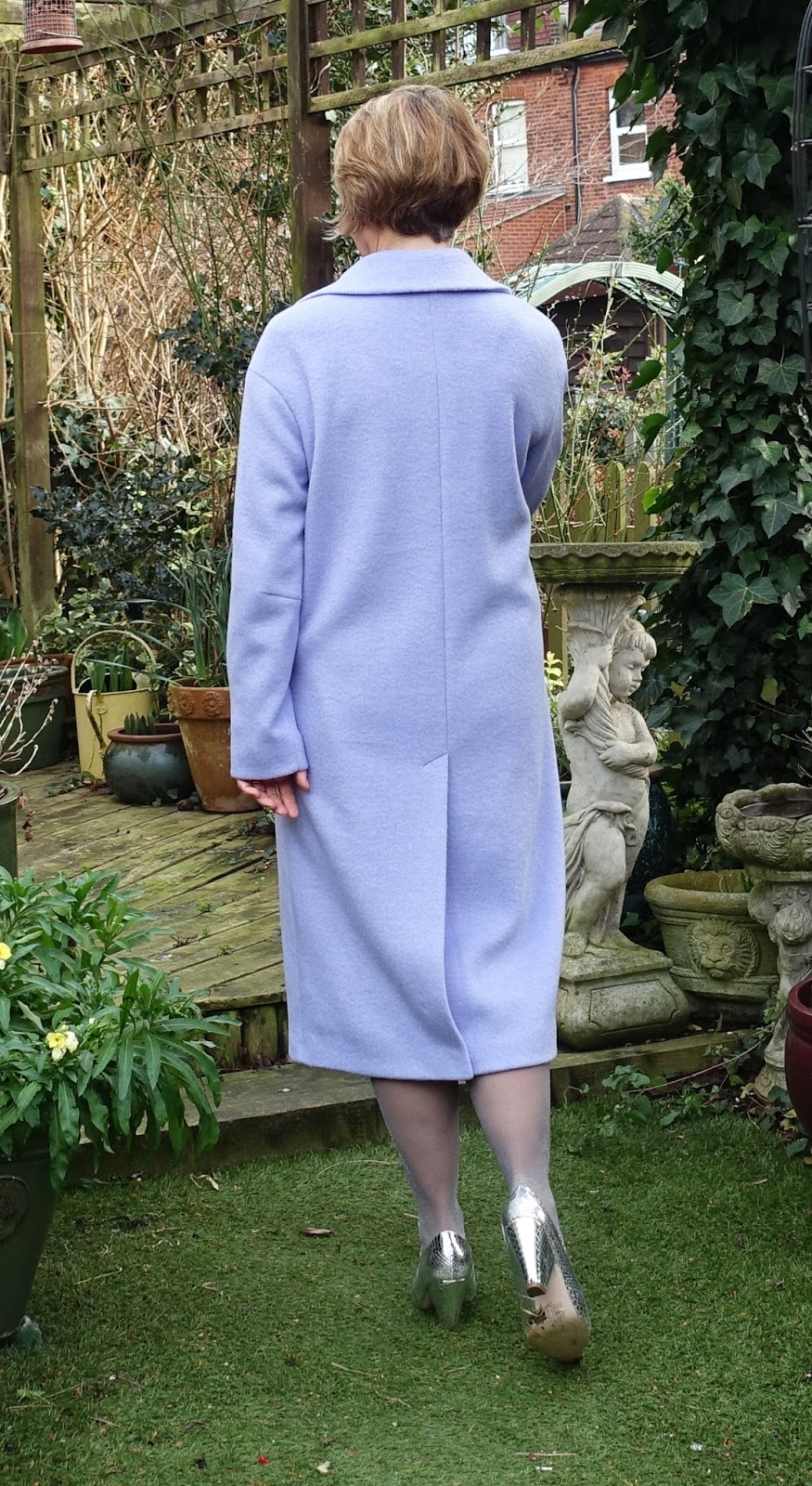 Image showing the back of a woman in long wool lilac coat and silver cone heeled shoes.