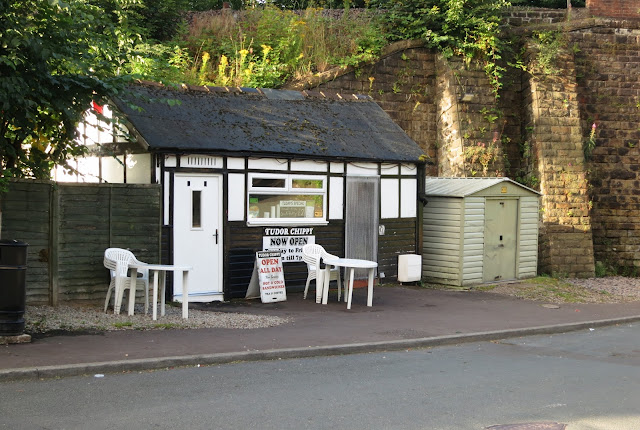 Chip shop hut with white tables and chairs outside in the shadow of railway bridge.